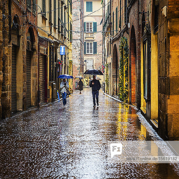 Menschen gehen durch die nassen Straßen von Lucca  einer Stadt und Gemeinde in der Toskana  Mittelitalien  am Serchio  einer fruchtbaren Ebene in der Nähe des Tyrrhenischen Meeres. Sie ist die Hauptstadt der Provinz Lucca. Sie ist berühmt für ihre intakten Stadtmauern aus der Renaissancezeit.