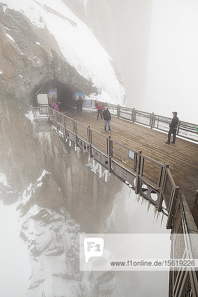 Visitors cross a bridge on the lower platforms at the Aiguille du Midi  Mont Blanc Massif  French Alps.
