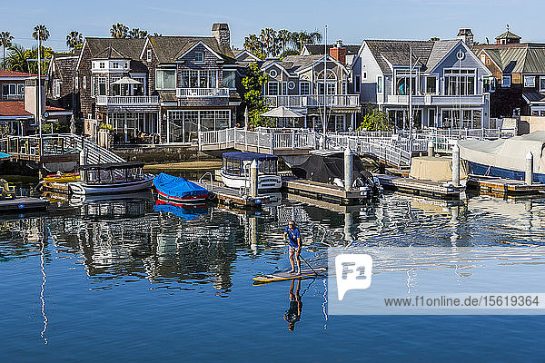 Distant view of single man paddleboarding in front of houses on waterfront  Long Beach  California  USA