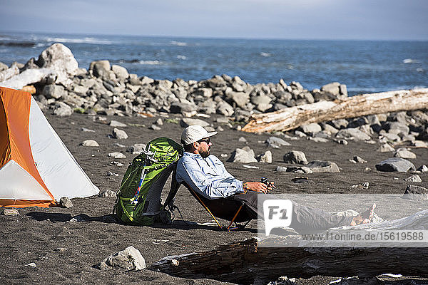 Man relaxing near the ocean during camping on the Lost Coast