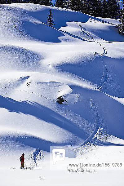 A man rides a backcountry line on his snowboard on Red Mountain Pass in Southwest Colorado.