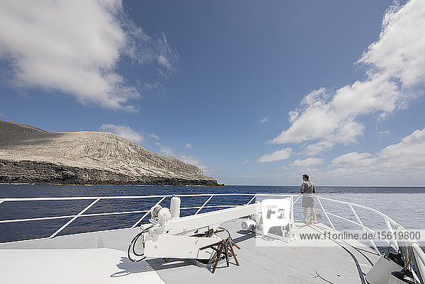 Photograph of single man looking at view of San Benedicto Island from ship  Revillagigedo Islands  Colima  Mexico
