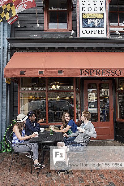 Friends socialize over coffee outside a cafe in Annapolis  Maryland.
