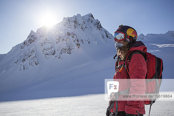 Professional Snowboarder Marie France Roy  looks out at the mountains after riding a fun run on a sunny day in Haines  Alaska.