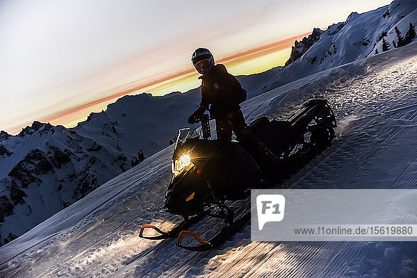 Single adventurous woman on snowmobile at sunset  Callaghan Valley  Whistler  British Columbia  Canada