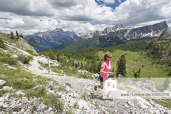 A Woman Trail Running At The Cinque Torri Area In The Dolomites  Italy