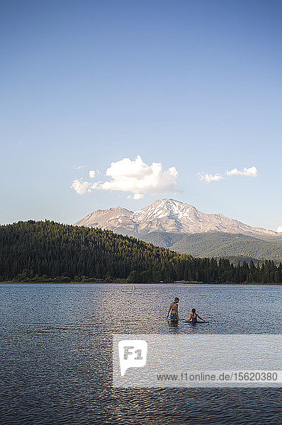 Distant view of couple swimming in Lakeï¾ Siskiyou with mountain peak in background  California  USA