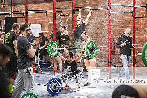Group of CrossFit athletes during competition with one lifting barbell and other doing chin-ups