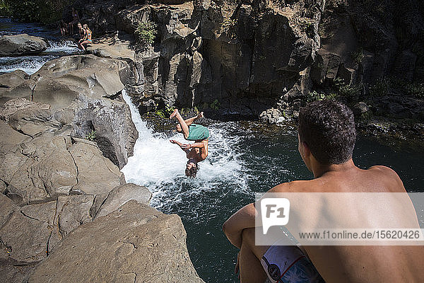 Young man cliff jumping near waterfall and another watching  ï¾ McCloudï¾ River  California  USA