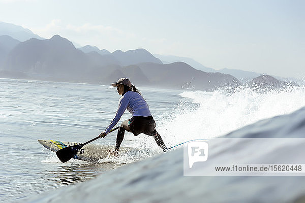 Side view shot of single woman paddle surfing in sea