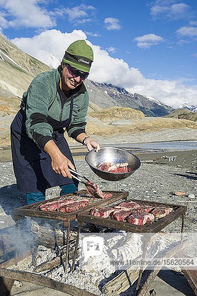 Woman Cooking Steaks Over Open Fire Along The Alsek River