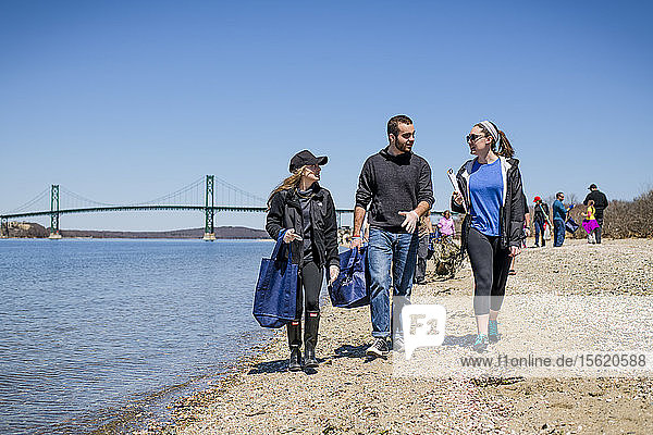 Two women and man walking with garbage bags during Earth Day beach cleanup  Portsmouth  Rhode Island  USA