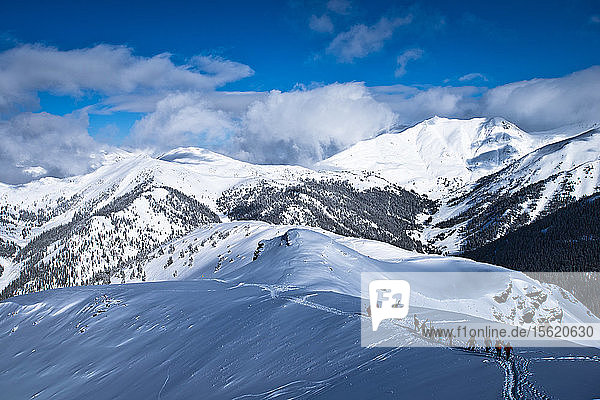 A group of skiers and snowboarders hike to the top of Silverton Mountain in Colorado.