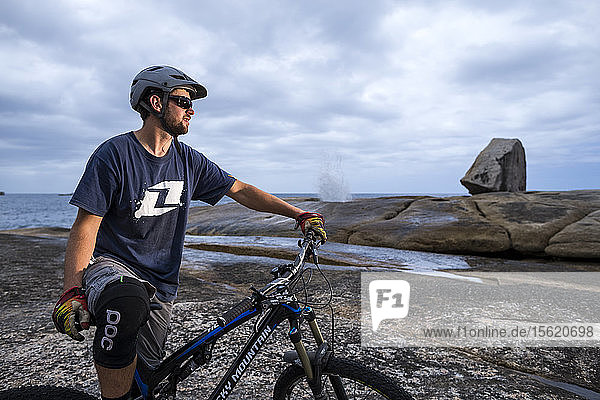 Male mountain biker riding on rocky foreshore near Bicheno blowhole on Tasmania's East Coast.