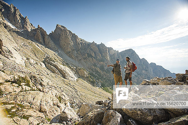 Two Male Hikers Stop To Find A Route In Grand Teton National Park