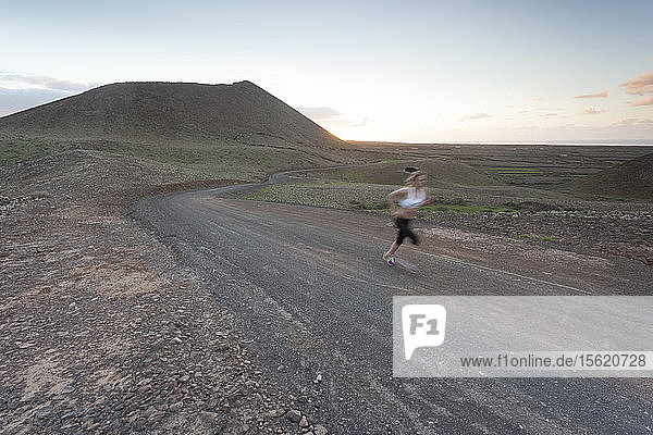 Athletic Girl running at sunset in a volcanic area in Fuerteventura  Canary Islands