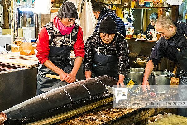 Man cutting fresh tuna at Tsukiji fish market in Tokyo  Japan