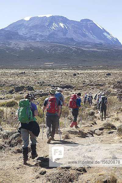Hikers are walking through a rocky and dusty grassland towards the base of Mount Kilimanjaro. Mount Kilimanjaro  with its three volcanic cones  Kibo  Mawenzi  and Shira  is a dormant volcanic mountain in Tanzania. It is the highest mountain in Africa  and rises approximately 4 877 meters (16 001 ft) from its base to 5 895 meters (19 341 ft) above sea level. The mountain is part of the Kilimanjaro National Park and is a major climbing destination. The mountain has been the subject of many scientific studies because of its shrinking glaciers. Tanzania is an East African country known for its vast wilderness areas. They include the plains of Serengeti National Park  a safari mecca populated by the ���big five��� game (elephant  lion  leopard  buffalo  rhino)  and Kilimanjaro National Park  home to Africa���s highest mountain.