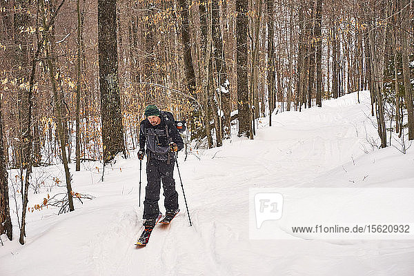 A man skinning his way through the Vermont backcountry on a splitboard.