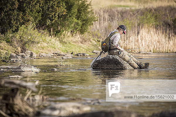 A woman fly fishes from the bank on the Madison River in Montana.