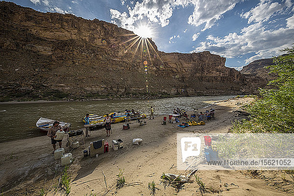 Sun shining over group of friends camping in Desolation Canyon on riverbank of Green River,  Utah,  USA