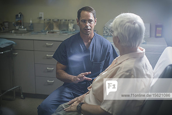 A physician discuss a point with his patient who sits in front of him.