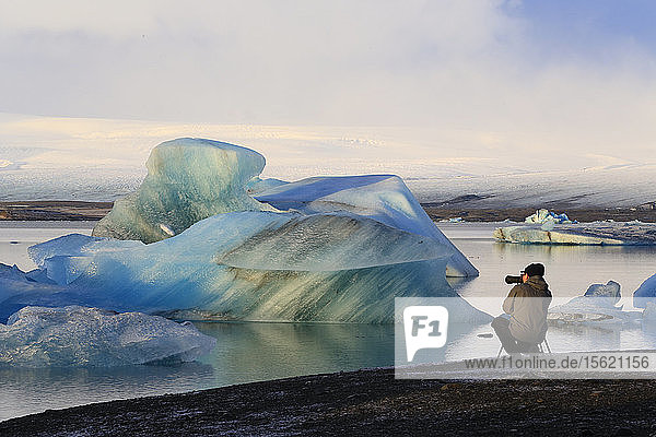 Photographer at J??kuls??rl??n glacier lagoon  Iceland  photographing icebergs that have come from the Brei??amerkurj??kull glacier which feeds into the lagoon.