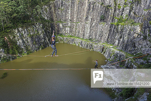 Adventurous man and woman crossing quarry in opposite directions on separate slacklines  Dibs Quarry  Maripora  Sao Paulo State  Brazil