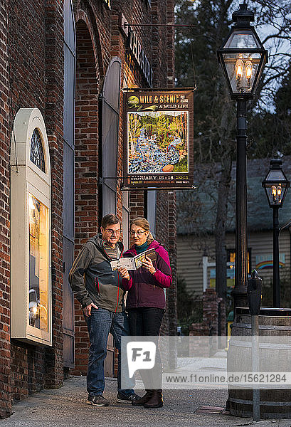 Retired couple reading Wild and Scenic Film Festival program on the streets of Nevada City California in front of Nevada Theater the oldest running theater west of the Mississippi River