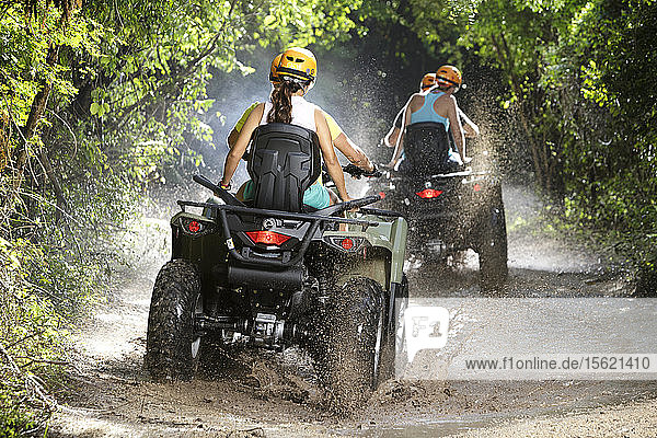 Rear view of couples driving quad bikes through dirt road puddles in Emotions Native Park  Quintana Roo  Mexico