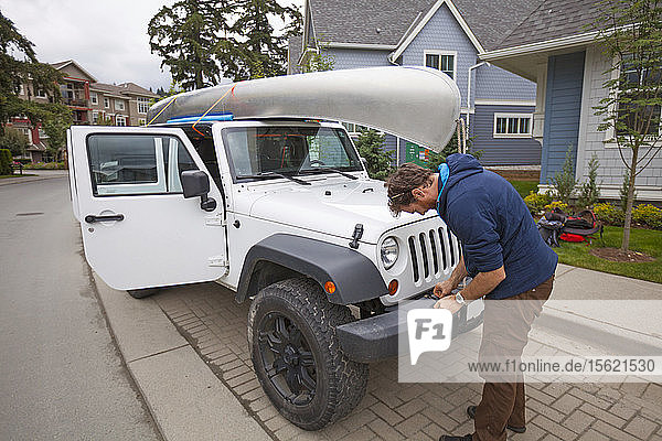 An Adventurer Ties His Canoe To The Roof Of His Jeep In A Suburban Neighborhood