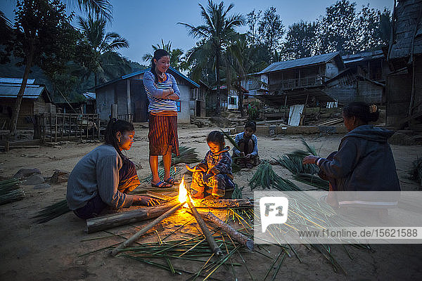 Women and children stay warm by a fire and process reeds used to manufacture brooms in Ban Had Dan  Laos. The clusters  wrapped with bamboo and made into brooms  are sold to neighboring Vietnam and fetch 3 000 kip ($0.37) - a cottage industry in this village. The village would only be partially inundated by proposed Dam #3 (whose construction has not yet commenced).