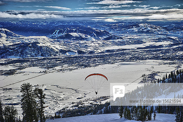 Tandem paragliders launch off of the side of a snow-covered mountain in Jackson Hole  Wyoming  with the mountain range in the background