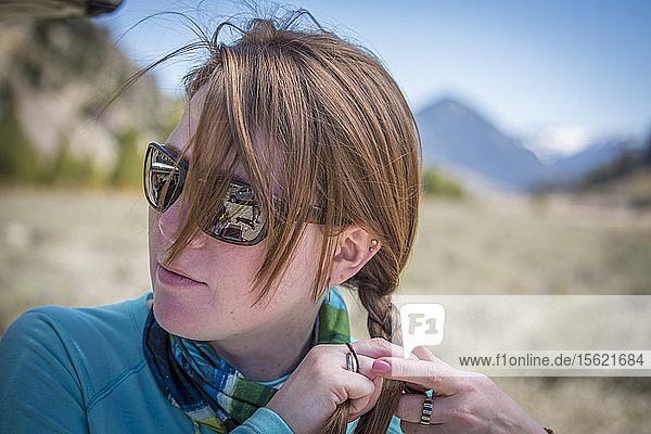 A woman braids her hair before fishing Montana's Gallatin River.