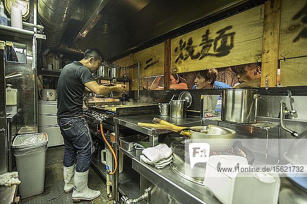 Side view shot of worker cooking in ramen shop  Tokyo  Japan