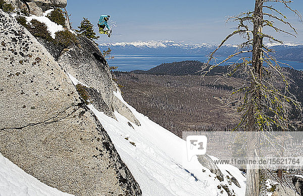 Snowboarder jumping off rock and over Lake Tahoe