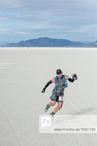 A male athlete runs across the Bonneville Salt Flats during the Salt Flats 100 in Bonneville  Utah.