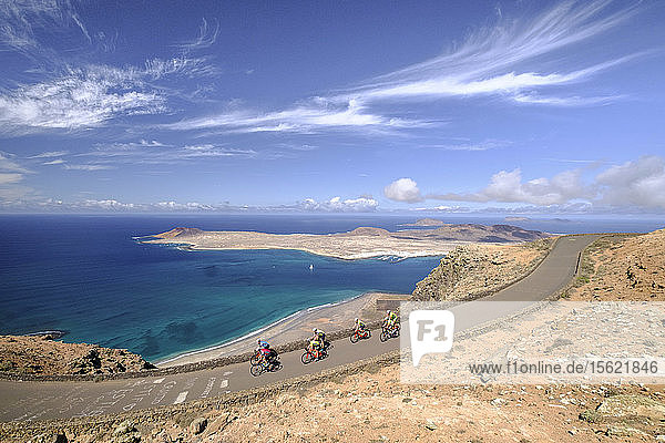 Group of cyclists pedaling on coastal road  Lanzarote  Canary Islands  Spain