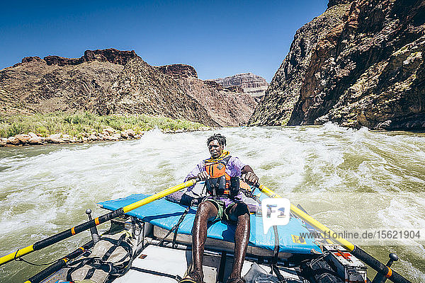 A man rows a raft through a rapid on the Colorado River  Grand Canyon National Park  Arizona  USA