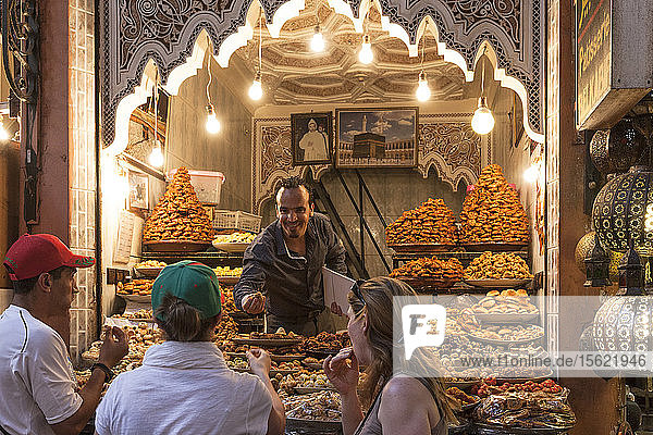 Moroccan seller trying to sell sweets and candits to some western tourist in Marrakesh souq  Marrakesh Morocco