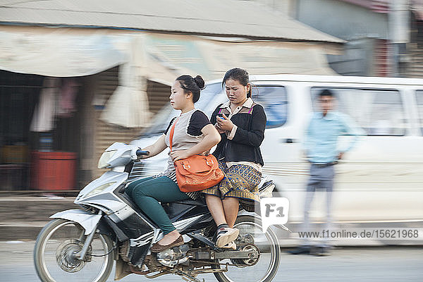 Young women ride a scooter together and check their phones on a busy street in Luang Prabang  Laos.