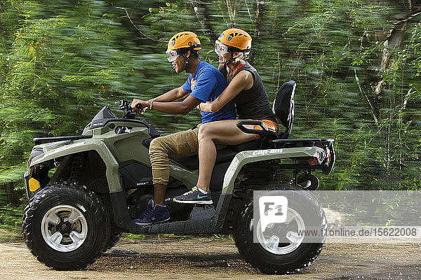Side view of couple riding quad bike in Emotions Native Park  Quintana Roo  Mexico