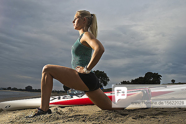A girl stretches on the beach in the morning before paddle boarding in San Diego  CA.
