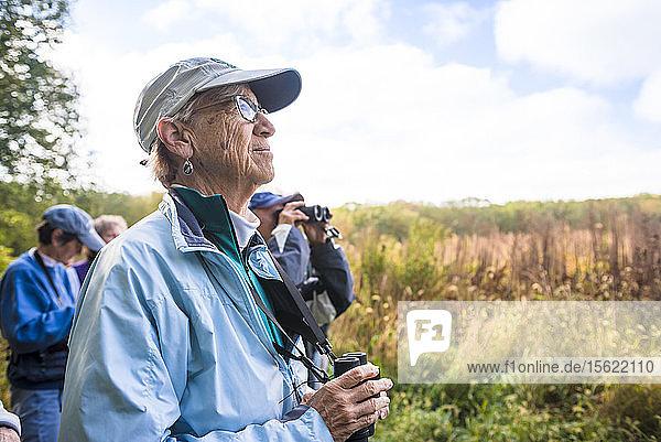 Senior man with binoculars during bird watching with Audubon Society  Johnston  Rhode Island  USA