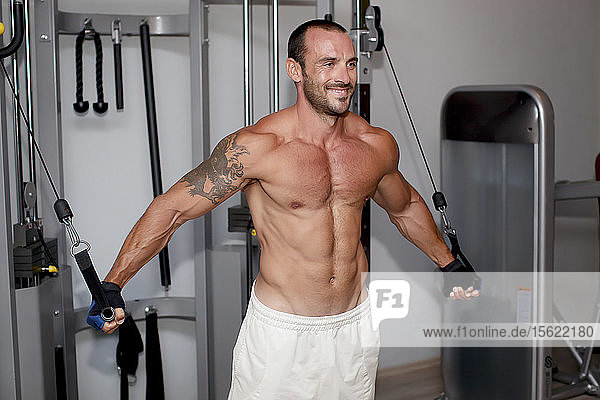Portrait of muscular man training on special sport equipment in gym