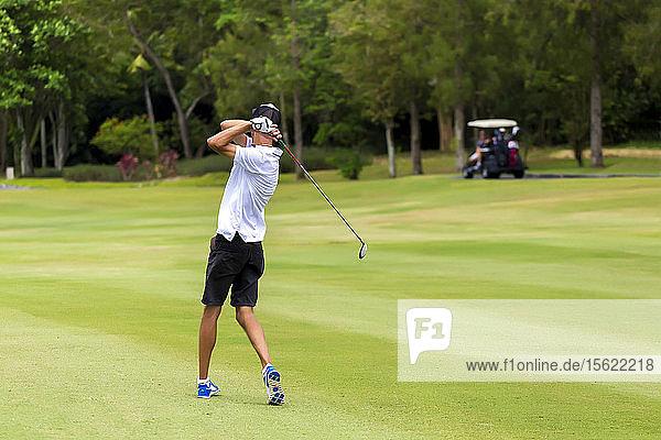 Young man playing golf  Bali  Indonesia