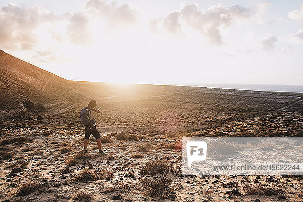 Woman photographing scenery with sand dunes at sunset  Tenerife  Canary Islands  Spain