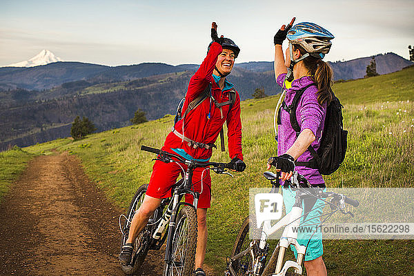 Two young women on mountain bikes give each other high-five while resting in a grassy meadow under early morning sky with volcano in distance.