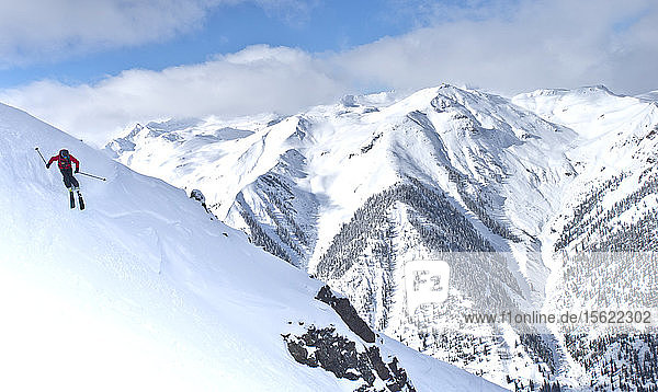 A skier riding down Silverton Mountain with other snow covered peaks in the background.