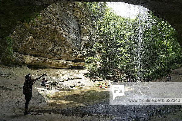 Frau hält Hand unter Wasserfall im Starved Rock State Park